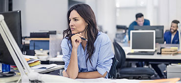 Woman sitting in front of computer in an office environment.