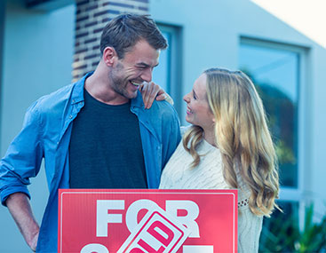 Couple standing in front of for sale sign of their new house.