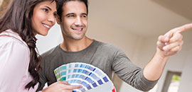 Young couple holding a paint swatch book for home decorating.